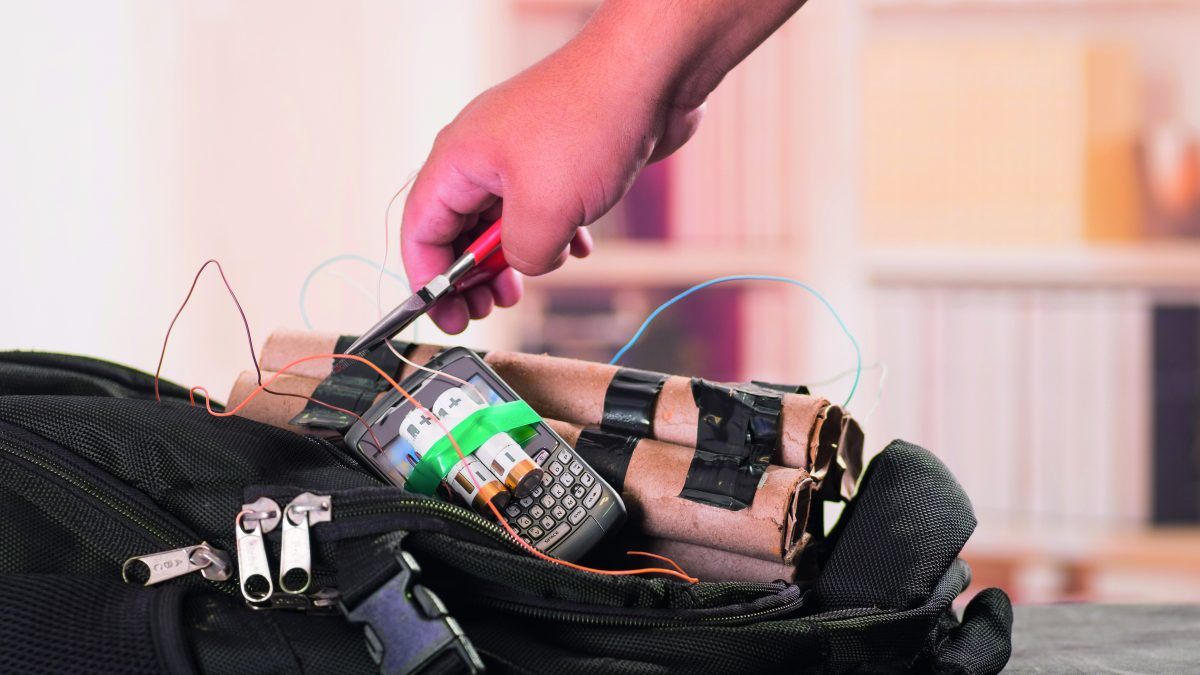 Close up shot of hands cutting wires with pliers of an improvised explosive device bomb