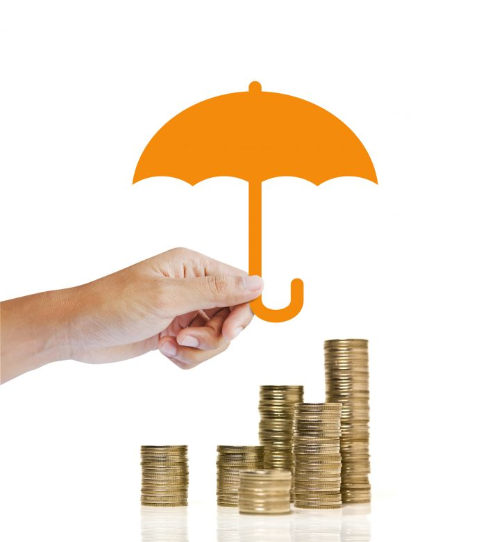 Stacks of golden coins covered by paper umbrella. insurance concept